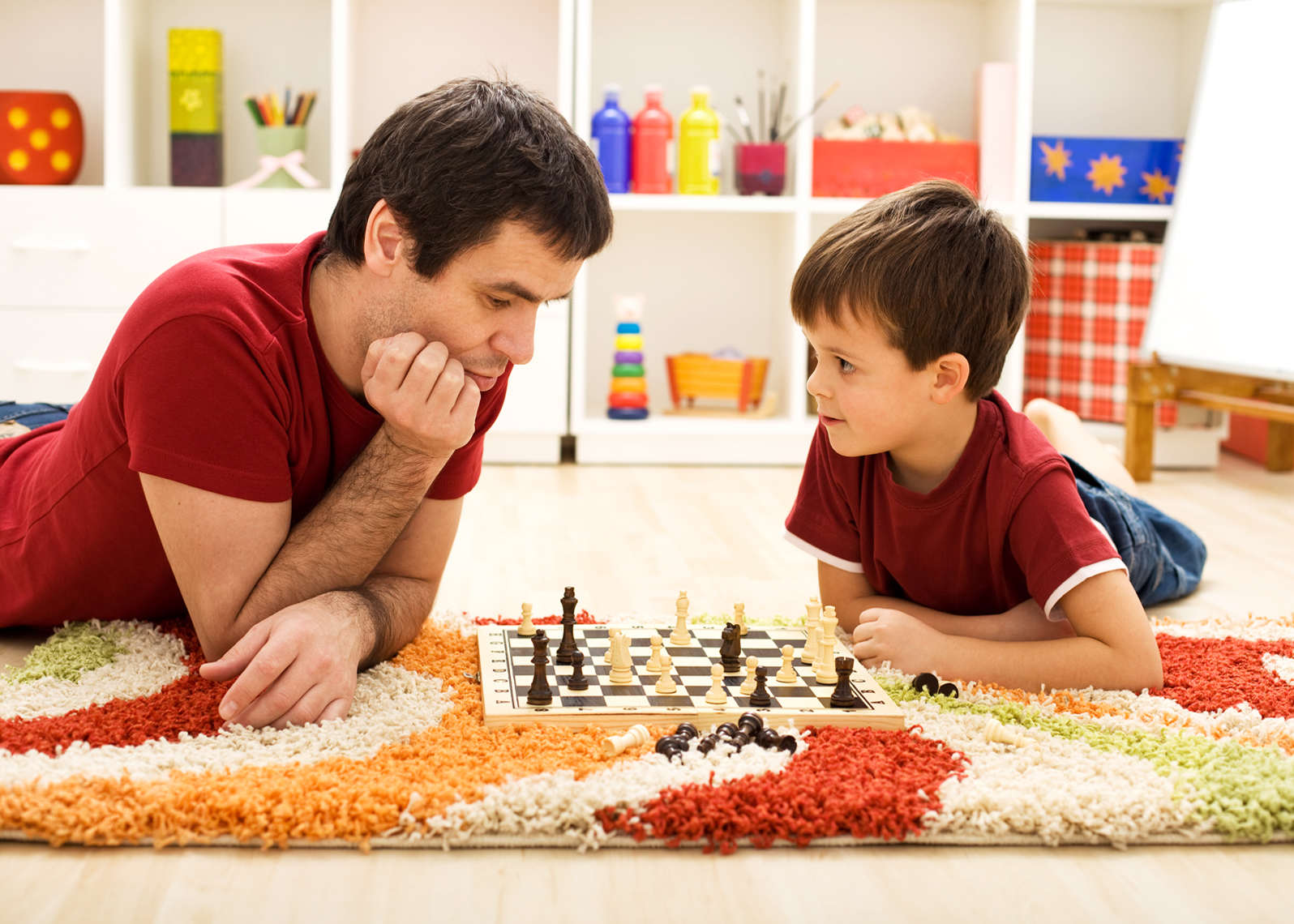 Man teaching boy the rules of chess - playing on the floor in the kids room